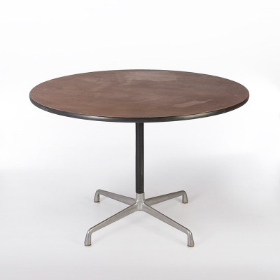 A circular Eames Universal Base table in an American Walnut natural veneer