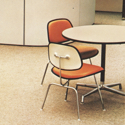 A Herman Miller catalog image from the late 1970's showing the white laminate Universal Base table and DCMU chairs