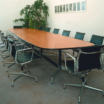 A 16 foot long conference table in a boat shape, shown fully surrounded with Alu Group desk/conference chairs