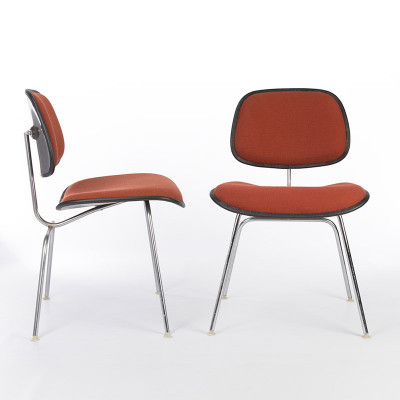 Pair of Eames two-piece plastic chairs in orange hopsack